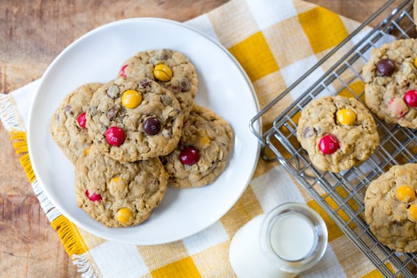 Peanut Butter M&M Oatmeal Cookies served with milk and decorated with a yellow white cloth