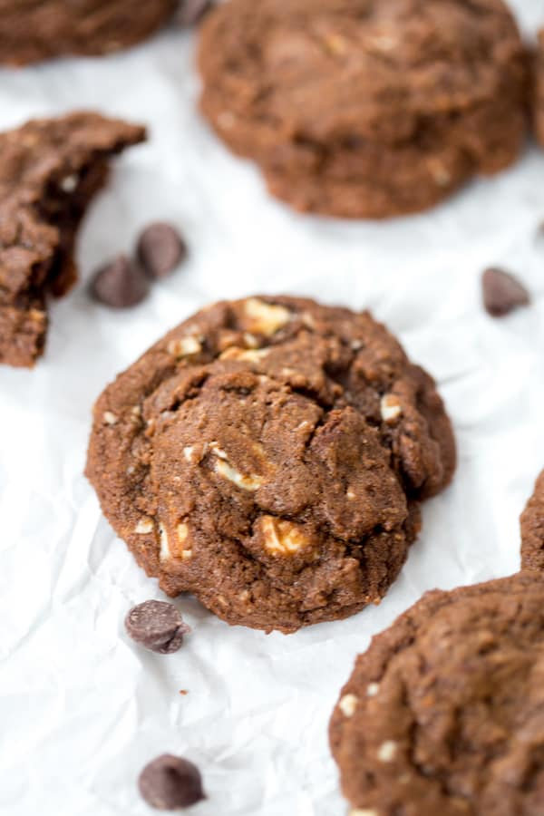 Triple Chocolate Cookies served on a white paper decorated with chocolate chips