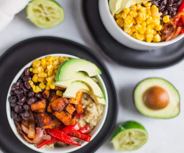Vegetarian Quinoa Burrito Bowls with Avocado Cream Sauce - Exquisite Recipe with the Ingredients Blurred in the Background