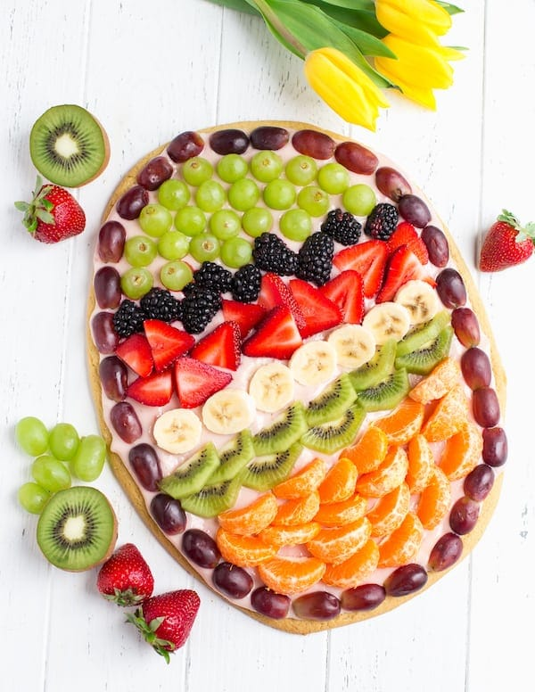 Easter Egg Fruit Pizza Overhead on the Dish with Strawberries and Kiwifruit on the Table
