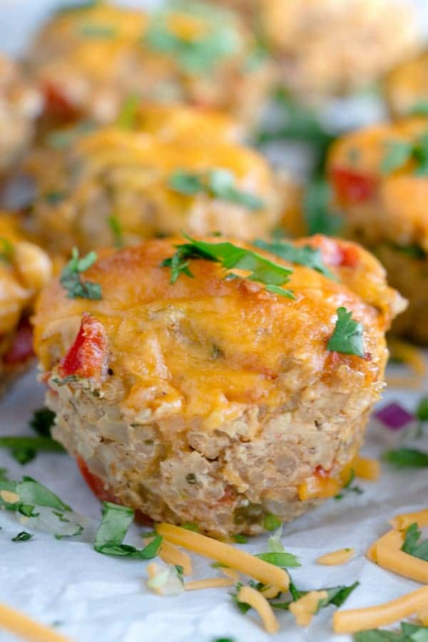 Cheesy Chicken Taco Meatloaf Muffins with Cheese and Greens Around on the Table